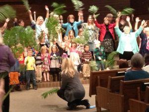 Lillan sjunger och viftar med sitt palmblad tillsammans med både vuxna och barn. Vilken stämning!