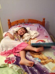 Lillan ligger ovanpå sitt nya Rapunsel täcke som går i samma ton som väggarna hennes....