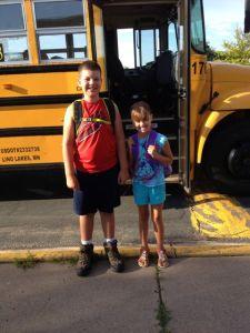Här står de utanför bussen. Klara att stiga på med ryggväskorna fulla med luncher, simkläder etc.