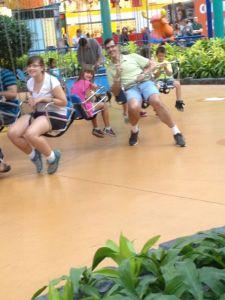 Maken och barnen på gungorna vid nöjesparken.