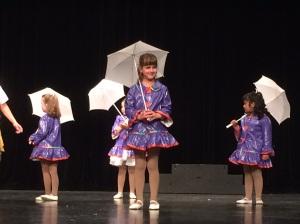 Lillasyster dansar med sin grup till 'Singing in the rain'.