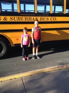 Glada barn framför skolbussen som skall skjutsa dem vidare till lägret.